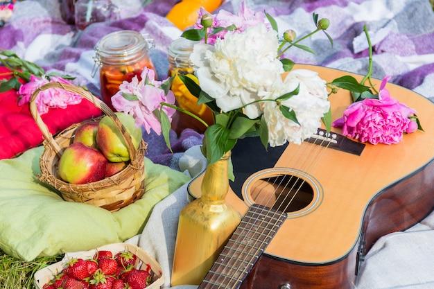 Picnic al aire libre con guitarra, manzanas, fresas, bebidas, almohadas y peonías.