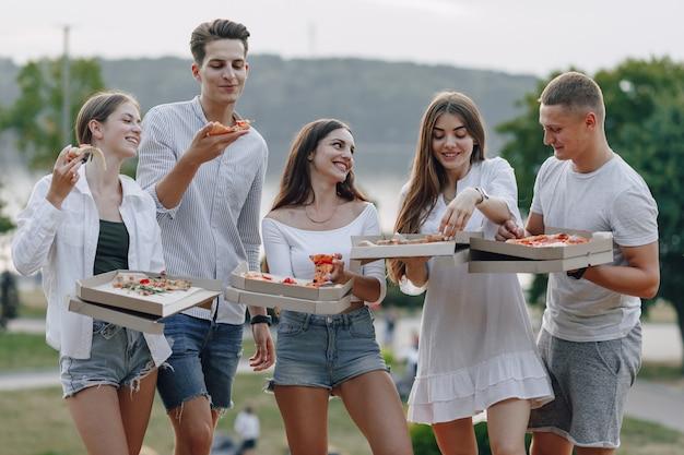 Picnic amigos con pizza y bebidas en un día soleado.