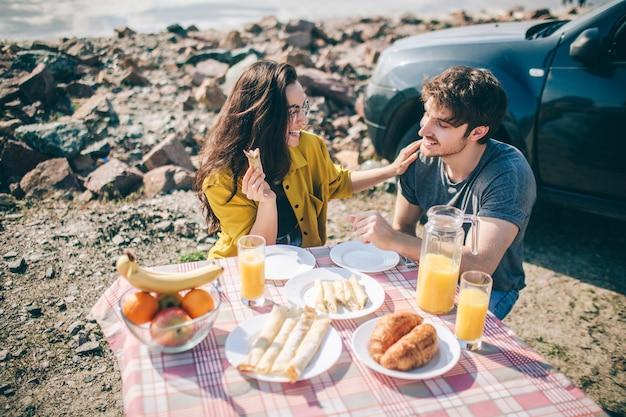 Picnic cerca del agua. familia feliz en un viaje por carretera en su coche. el hombre y la mujer viajan por el mar o el océano o el río. paseo de verano en automóvil.