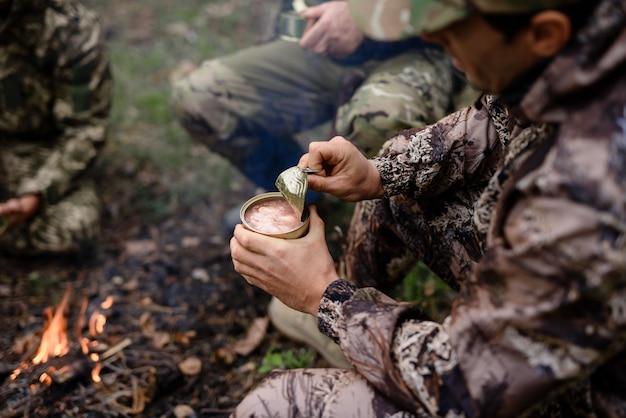 Picnic cerca de la hoguera cazador abre lata en el bosque.