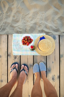Picnic cerca del sombrero de mar, vino, copas, fresa.