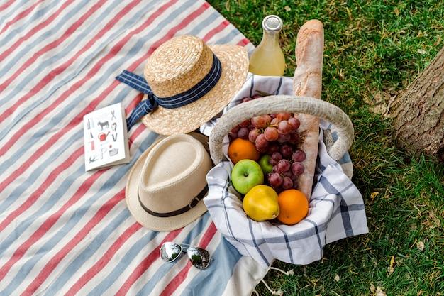 Picnic con cesta de frutas y limonada en el parque