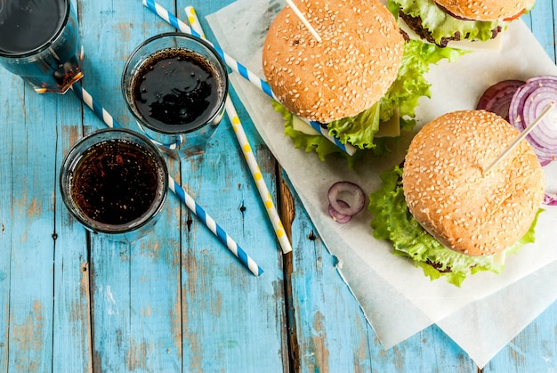 Picnic comida rápida comida poco saludable deliciosas hamburguesas sabrosas frescas con chuleta de res verduras frescas y queso en la vieja mesa rústica de madera azul con agua de soda dulce