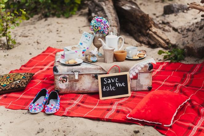 Picnic de naturaleza muerta romántico en una playa. tazas, galletas, maleta en la cubierta roja