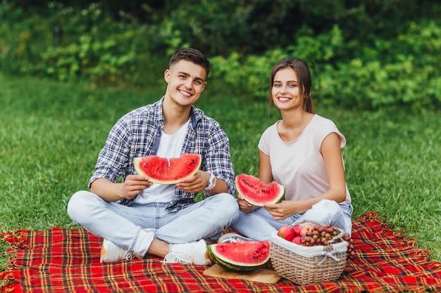 Picnic divertido con sandía. hombre y mujer comiendo paz de sandía en el parque