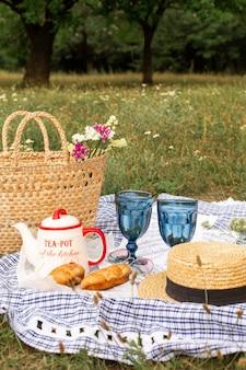 Picnic con estilo en el verde césped. cruasanes recién hechos y una tetera con té en una colcha cerca de un sombrero de mimbre femenino. contenido de instagram