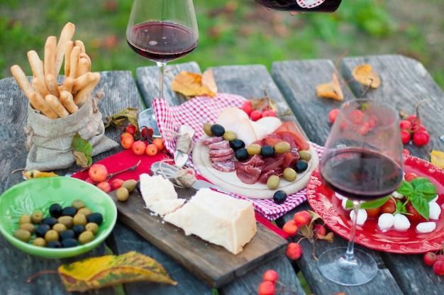 Picnic italiano con vino tinto, parmesano, jamón y aceitunas. almuerzo al aire libre. bocadillos tradicionales. un hombre vierte una copa de vino. copia espacio