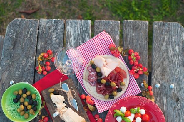 Picnic italiano con vino tinto, parmesano, jamón, ensalada caprese y aceitunas. almuerzo al aire libre y mesa de madera. bocadillos tradicionales. copia espacio