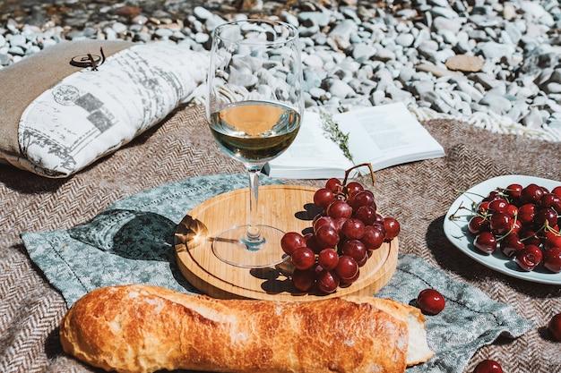 Picnic romántico en la costa con copa de vino blanco baguette cerezas uva libro abierto almohada