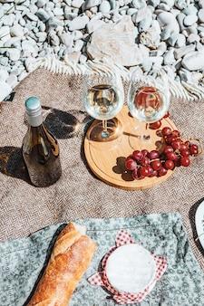 Picnic romántico en la costa dos copas de vino blanco botella baguette queso uva