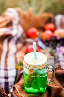 Picnic de verano al aire libre, tarro de bebida de verano con limonada, cuadros a la cálida luz del sol