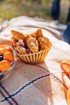 Picnic de verano en una alfombra con frutas, vino y té, tazas, croissants y detalles de dulces.