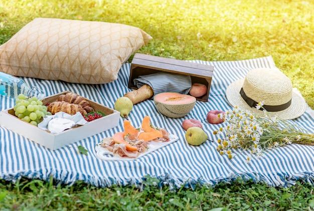 Picnic de verano en la hierba, jamón con melón, uva, panadería, frutas.