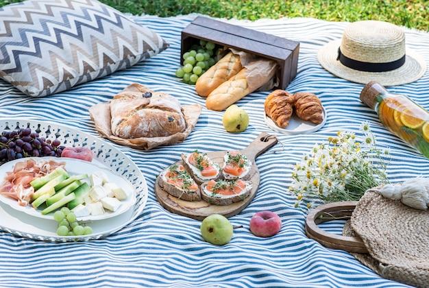 Picnic de verano en la hierba, sándwiches con salmón, uva, panadería y frutas.