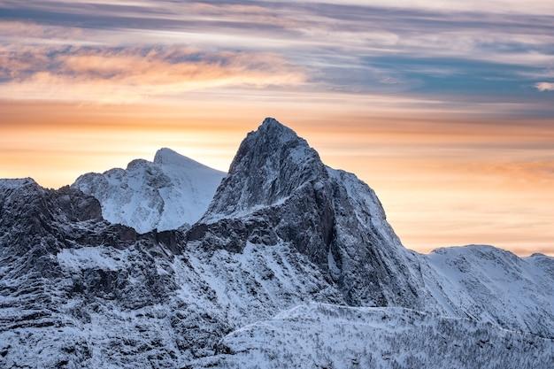 Pico escarpado de nieve con cielo colorido en la mañana
