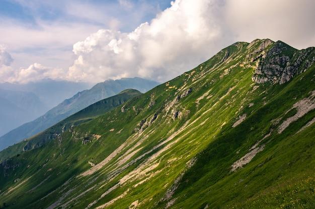 Pico de montaña con la ladera cubierta de hierba verde