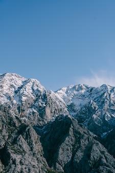 Picos nevados en invierno de boka kotorska en montenegro en la bahía de kotor
