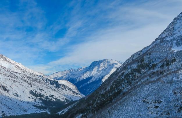 Picos nevados de las montañas caucásicas en el cielo azul de las nubes. garganta de syltran