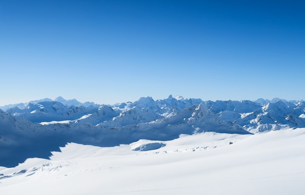 Picos nevados de montañas caucásicas en el cielo azul. región de elbrus