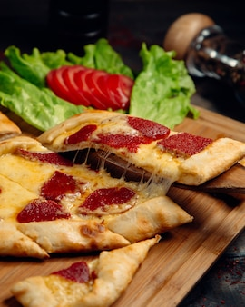 Pide pizza turca con pepperoni y queso derretido.