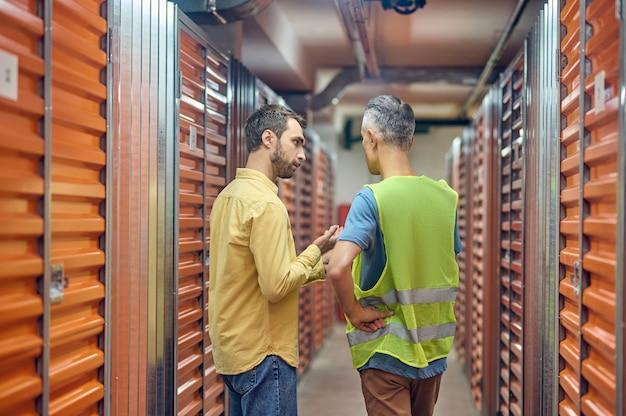 Pidiendo al comprador y al trabajador del almacén de pie con la espalda