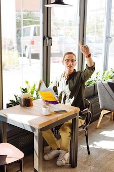 Pidiendo cheque. agradable hombre de pelo largo sosteniendo un libro mientras espera al camarero