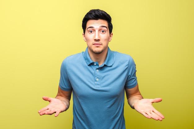 Pidiendo gesto de hombre guapo en camisa polo azul sobre fondo amarillo. cuál es el problema