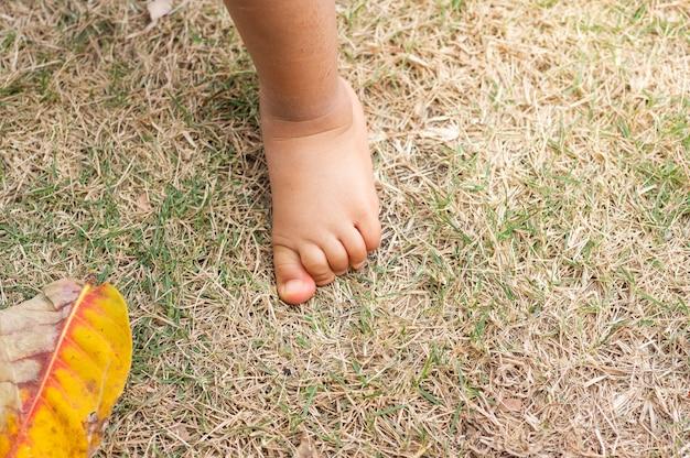 Pie de bebé sobre la hierba con espacio de copia