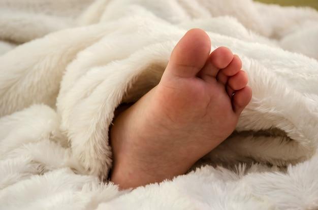 Pie de bebé visible desde debajo de las mantas