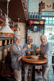 De pie y bebiendo. tres hombres jubilados de pelo gris que se sienten emocionados mientras están de pie y bebiendo cerveza