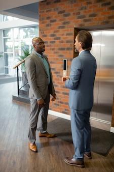 De pie cerca del ascensor. hombre de piel oscura hablando con socio de negocios de pie cerca del ascensor