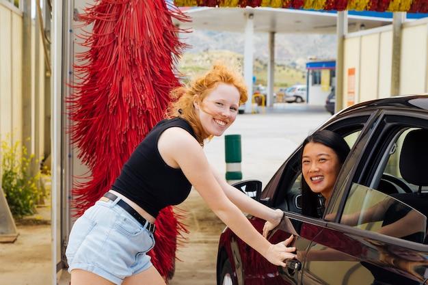 De pie cerca del coche femenino y sentado en el coche mujer mirando la cámara