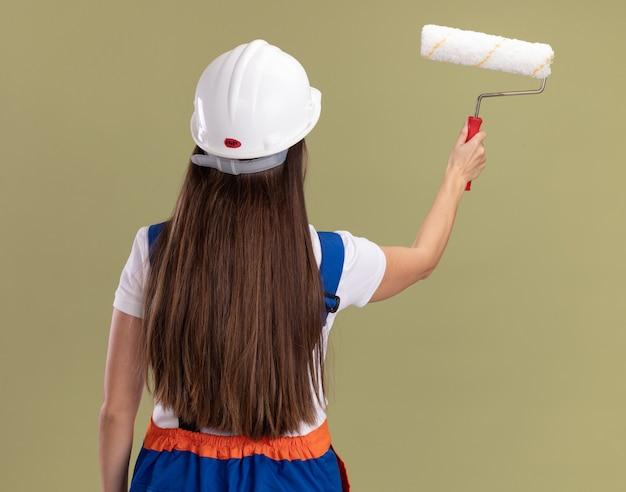 De pie detrás de la vista joven constructor mujer en uniforme sosteniendo cepillo de rodillo aislado en la pared verde oliva