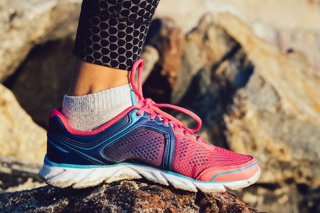 Pie femenino en la zapatilla de deporte rosada y azul que se coloca en mañana soleada de las piedras rocosas