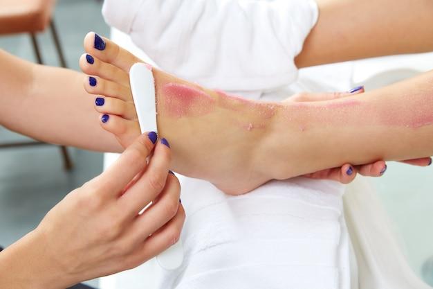 Pie friega pedicura mujer pierna en salón de uñas