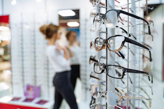 De pie con gafas en la tienda de óptica.