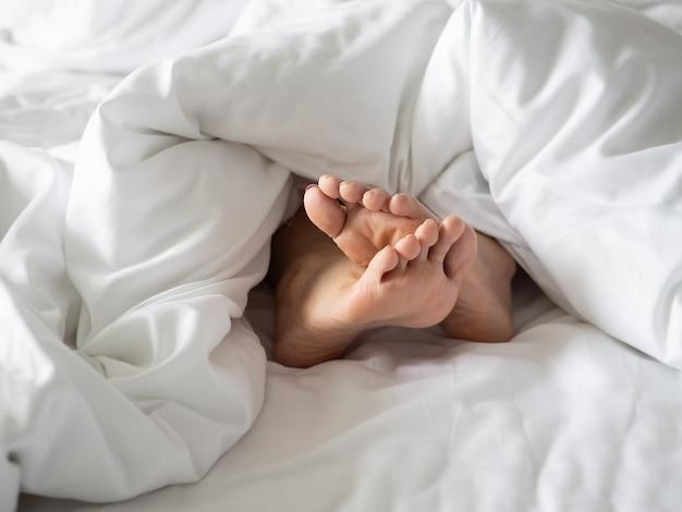 Pie en manta en cama acogedora en la mañana