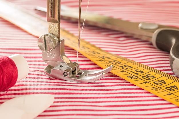 El pie de la máquina de coser con una aguja cose tela