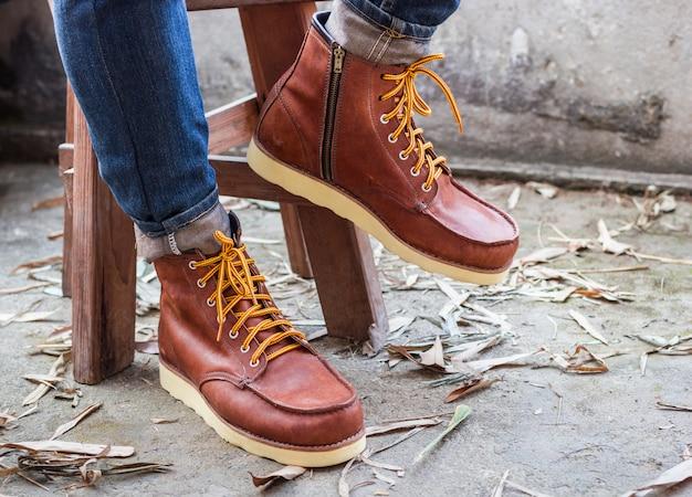 Pie masculino con zapatos de cuero marrón y jeans.