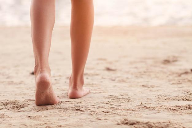Pie de mujer caminando por la playa.
