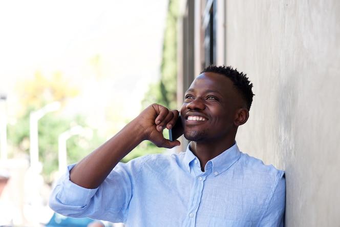 Pie negro joven fuera de la pared y hablando por teléfono móvil