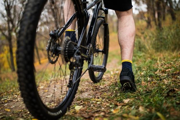Pie en el pedal de la bicicleta en el parque, verano activo. de cerca.