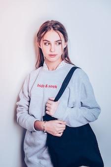 De pie de perfil. encantadora adolescente posando en sudadera con capucha larga gris con bolsa negra
