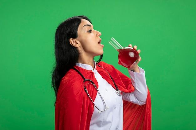 De pie en la vista de perfil joven superhéroe vestida con bata médica con estetoscopio sosteniendo y bebiendo una botella de vidrio de química llena de líquido rojo aislado en verde