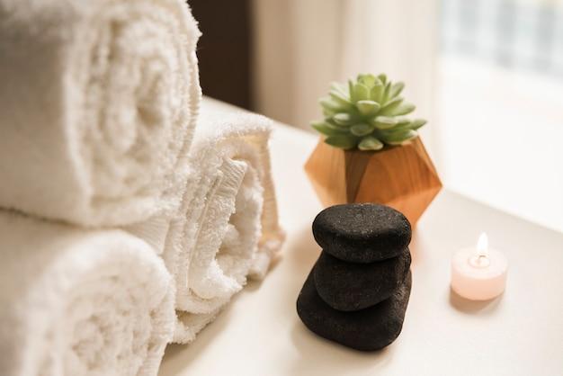 Piedra caliente negra; vela encendida planta de cactus y toalla enrollada blanca.