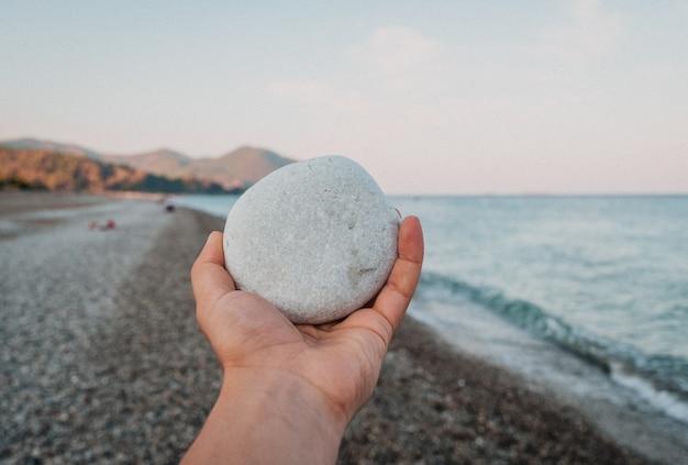 Piedra de guijarros blancos en mano sobre fondo de paisaje increíble en la playa en día de verano.