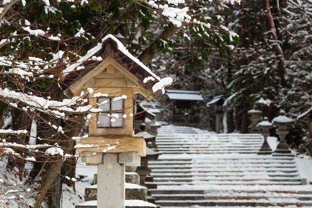 Piedra japonesa y linterna de madera con nieve en el santuario hida-sannogu hie-jinja