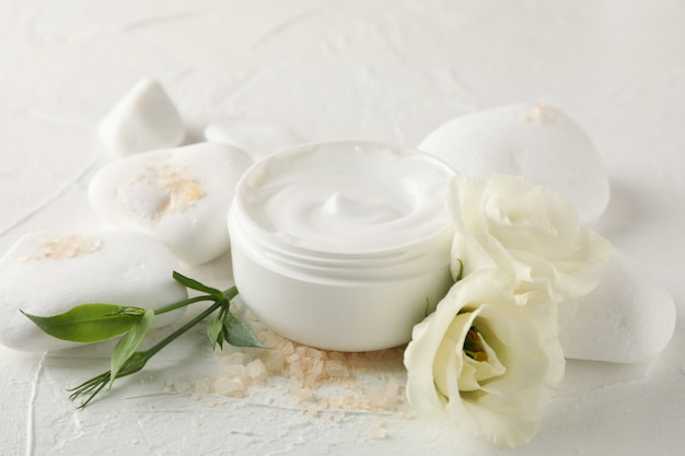 Piedras, crema, sal y flores sobre fondo blanco, de cerca