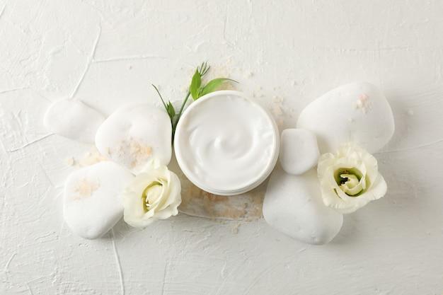 Piedras, crema, sal y flores sobre fondo blanco, espacio de copia