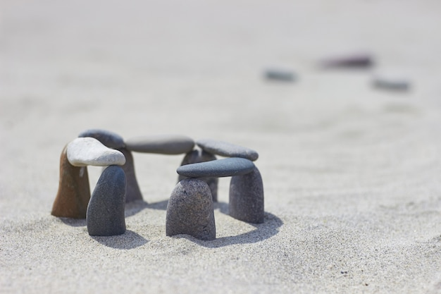 Piedras equilibradas sobre arena. pequeño stonehenge